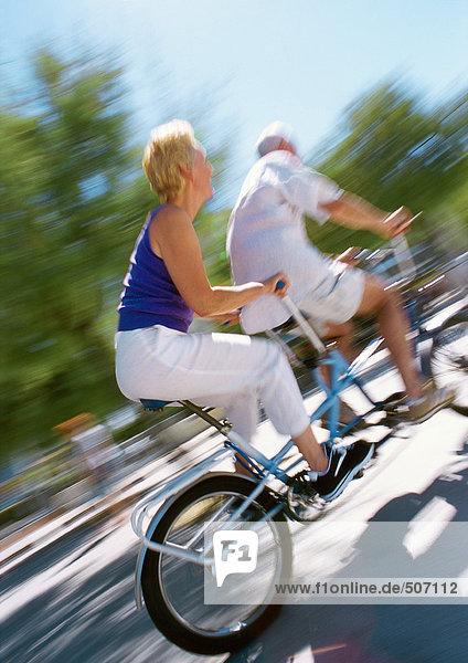 Erwachsener Mann und Frau  die zusammen auf einem Tandemrad fahren  verschwommen