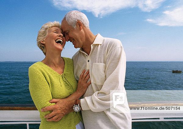 Ein reifes Paar umarmt sich  lacht auf dem Bootsdeck.