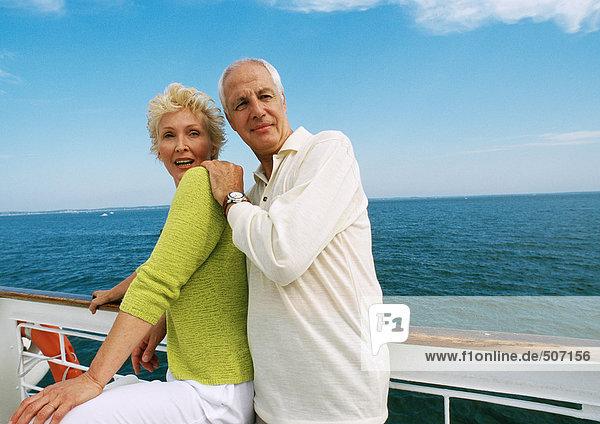 Reife Paare stehen zusammen neben der Reling auf dem Bootsdeck.