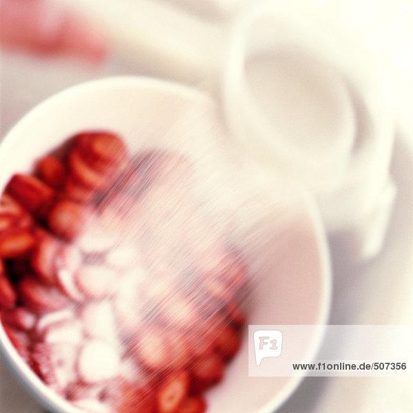 Erdbeeren werden mit Zucker bestreut  verschwommen.