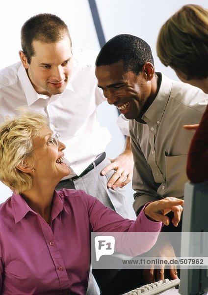 Reife Geschäftsfrau und drei Geschäftsleute  lachend