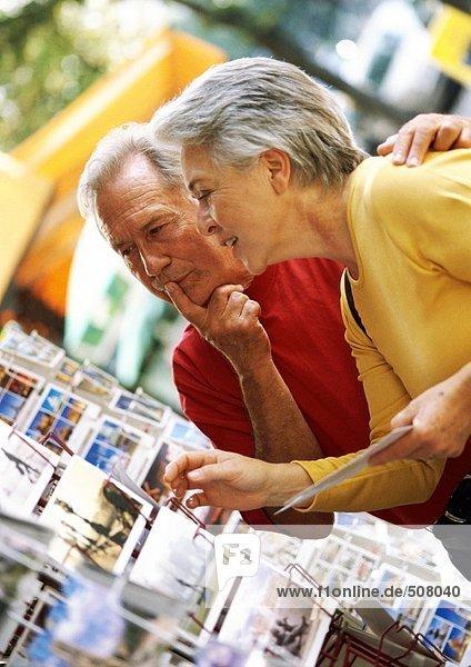 Reife Frau und Mann beim Betrachten von Postkarten