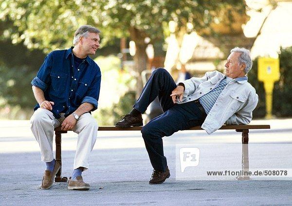 Reife Männer sitzen auf einer Bank