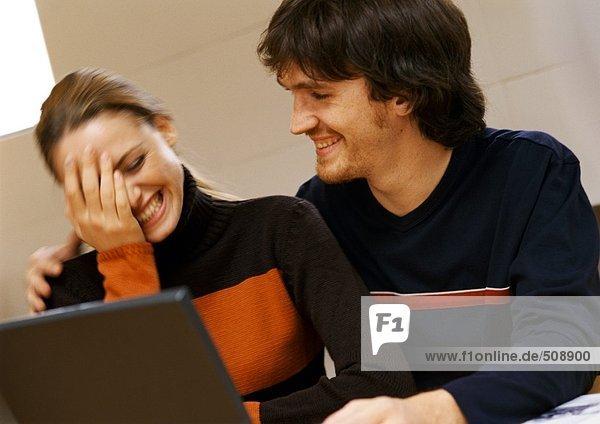 Mann und Frau lächelnd  Frau mit Hand im Gesicht