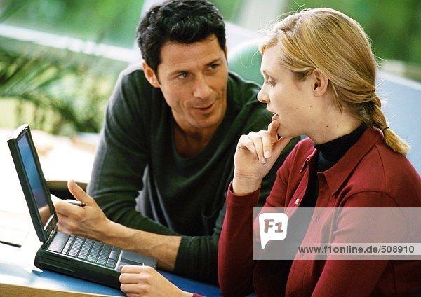 Mann und Frau beim Sprechen und Benutzen des Laptops