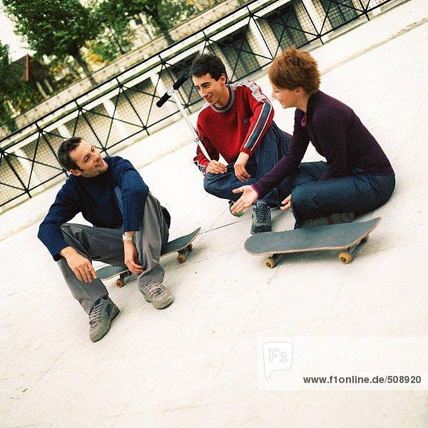 Jugendliche sitzen im Freien mit Skateboards