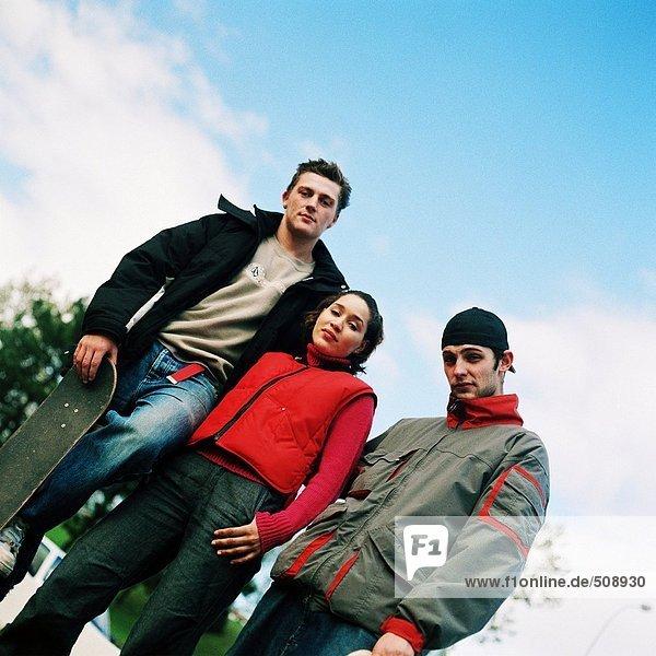 Drei junge Leute  einer hält Skateboard  Tiefblick  Portrait