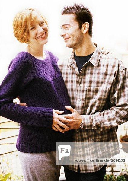 Mann und schwangere Frau  die mit Armen umeinander stehen