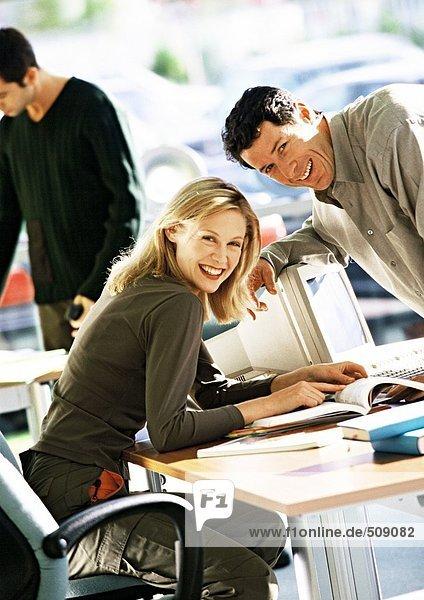Frau sitzt am Schreibtisch  Mann lehnt sich über den Schreibtisch  beide lächeln in die Kamera.