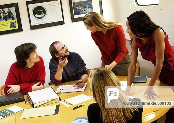People in conference room  gathered around table
