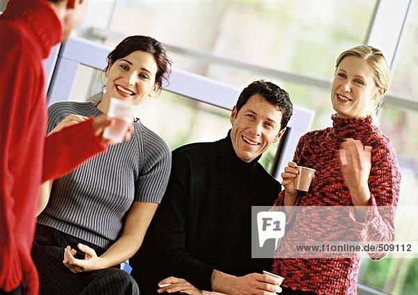 Vier Personen halten Plastikbecher  Portrait