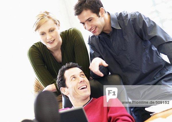 Mann im Sessel  zweiter Mann und zweite Frau schauen ihm über die Schulter