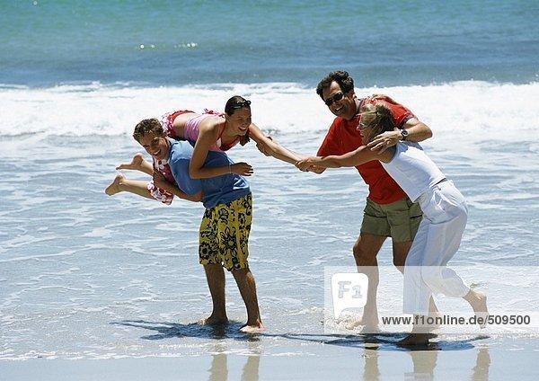 Familie spielt zusammen am Strand.
