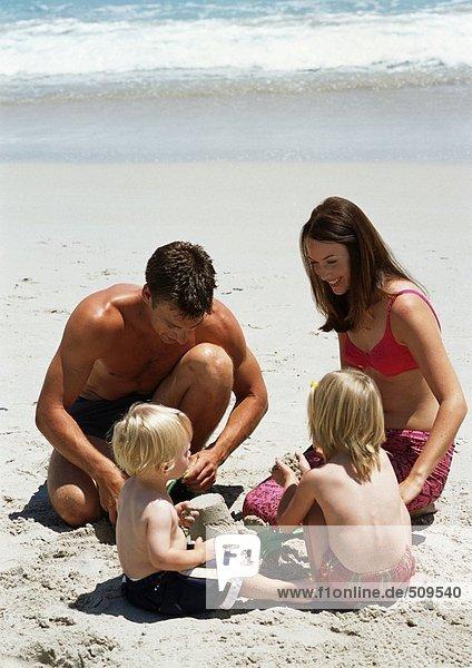 Junge Familie beim Bau einer Sandburg am Strand