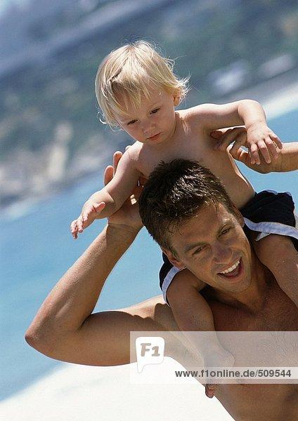 Mann  der ein kleines Kind auf den Schultern am Strand trägt.