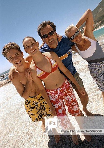 Familie steht am Strand.