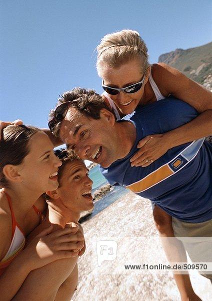 Nahaufnahme von zwei Männern  die Frauen auf dem Rücken am Strand tragen.