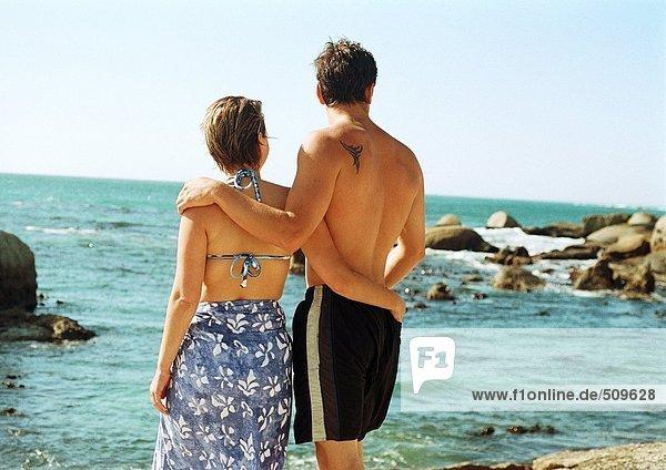 Mann und Frau vor dem Meer stehend  Rückansicht