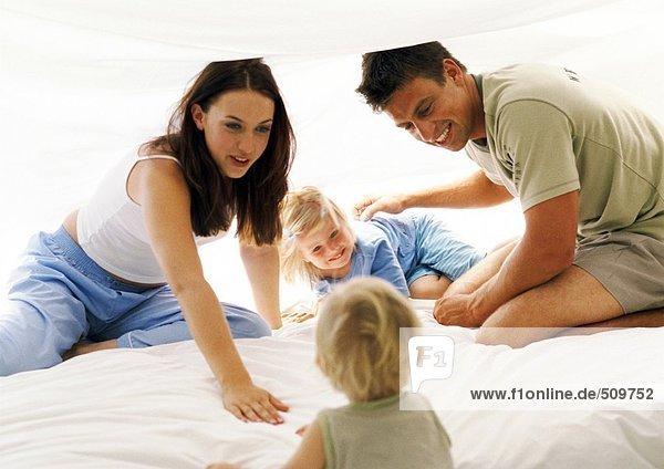 Eltern und zwei kleine Kinder im Bett  lächelnd