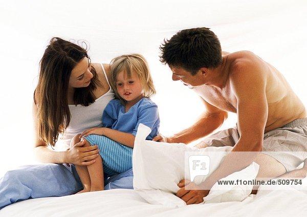 Familie zusammen auf dem Bett,  Mutter mit Tochter auf dem Schoß, Familie zusammen auf dem Bett,  Mutter mit Tochter auf dem Schoß