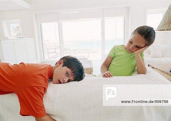 Zwei Kinder liegen auf dem Bett  eines schaut in die Kamera.
