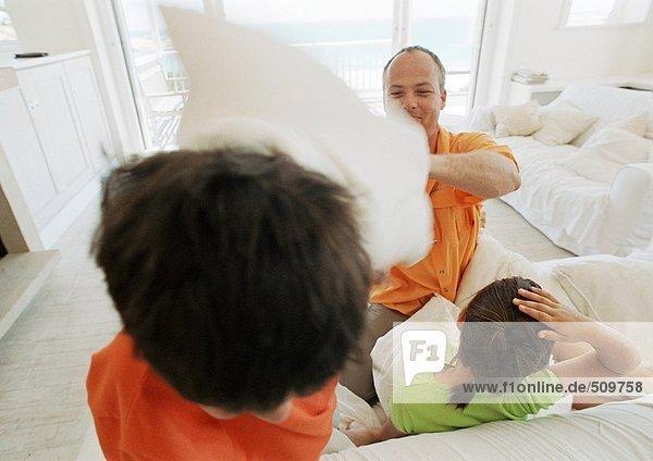 Vater und Kinder beim Kissenschlachten