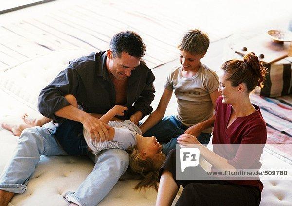 Eltern und Kinder beim Spielen auf der Matratze