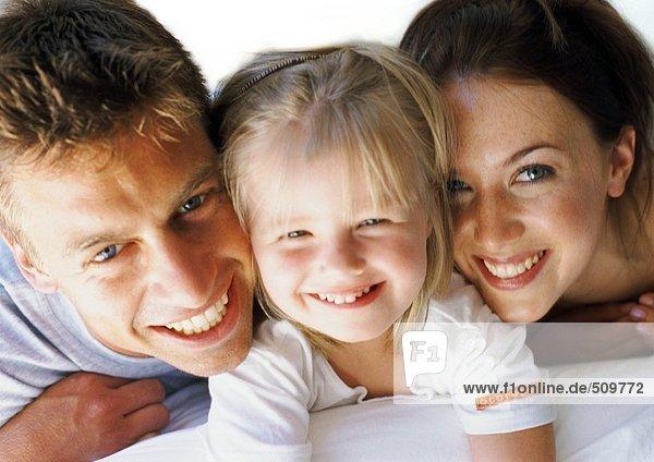 Kleines Mädchen zwischen den Eltern liegend  lächelnd  Nahaufnahme