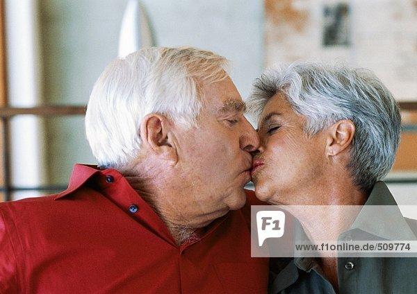 Seniorenpaar beim Küssen  Seitenansicht