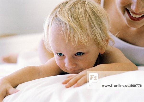 Frau und Baby auf dem Bett liegend  Nahaufnahme  abgeschnitten