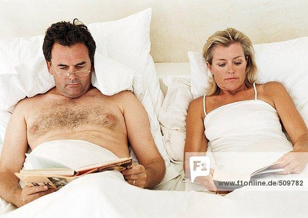Paar im Bett liegend  lesend