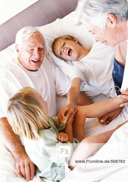 Großeltern und Kinder  die auf dem Bett spielen  lächelnd