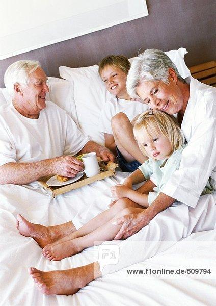 Großeltern und Kinder im Bett sitzend  Mann mit Frühstückstablett
