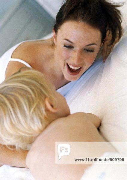 Mutter und Baby spielen im Bett  Nahaufnahme