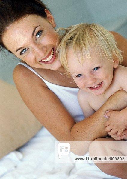 Mutter umarmt Baby  lächelnd vor der Kamera