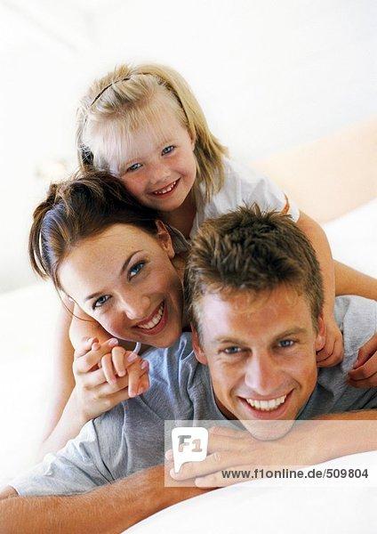 Eltern und Tochter liegen übereinander  lächelnd vor der Kamera.