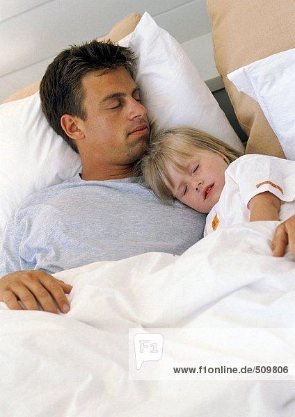 Vater und Tochter schlafen im Bett
