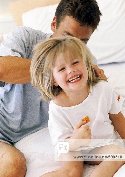 Vater und Tochter im Bett  Mädchen lächelnd