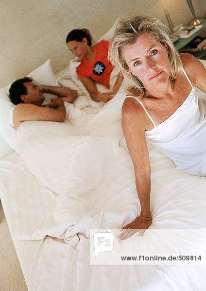 Frau auf dem Bett sitzend  Familie im Bett liegend im Hintergrund