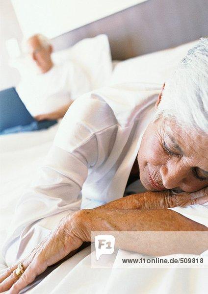 Seniorin schläft auf dem Bett  Mann nutzt Laptop im Hintergrund