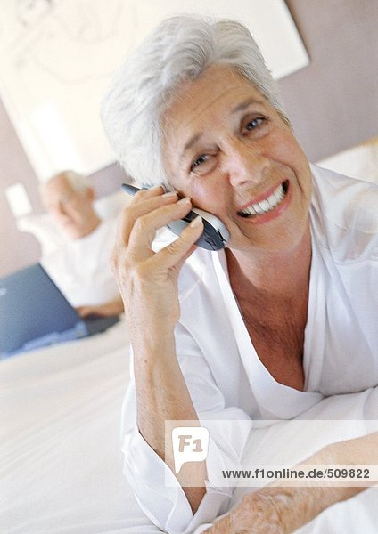 Seniorin mit Handy  lächelnd  Ehemann mit Laptop im Hintergrund