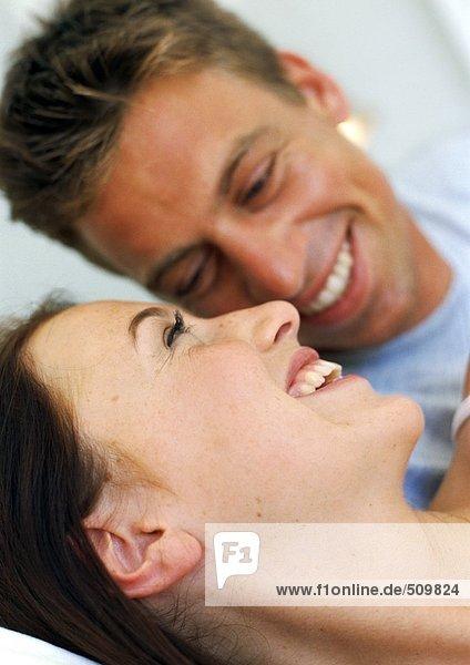 Paar lächelnd im Bett liegend  Nahaufnahme