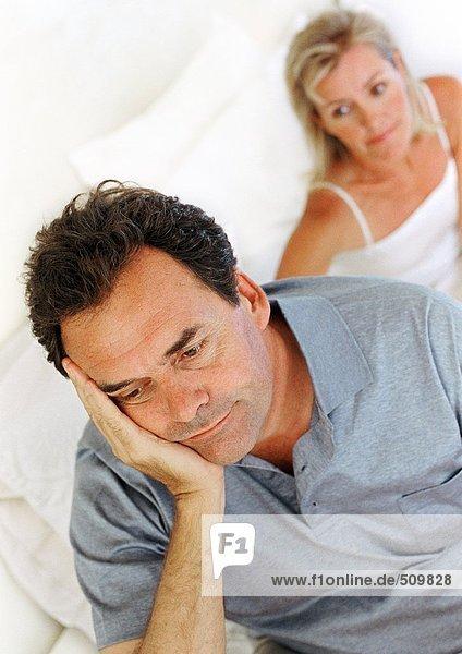 Mann auf dem Bett sitzend  Kopf haltend  Frau im Hintergrund