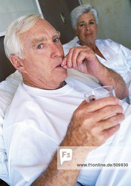 Seniorenpaar im Bett  Mann nimmt Pille