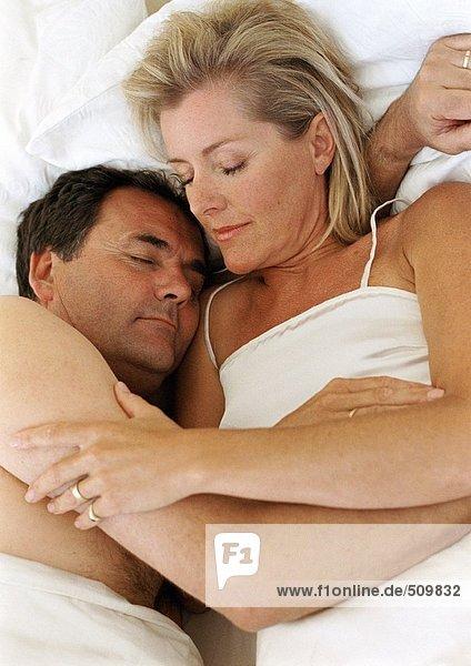Ein Paar schläft im Bett  in den Armen des anderen.