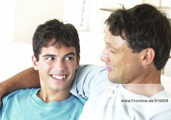 Vater und Teenager lächeln sich an  der Arm des Mannes um den Jungen.