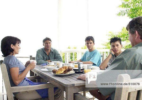 Familie am Tisch sitzend  draußen