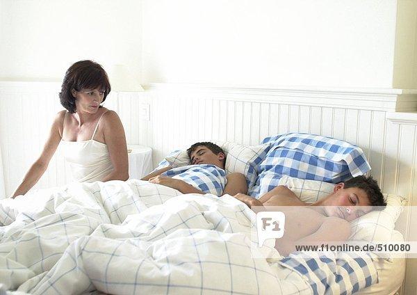 Frau sitzt auf der Bettkante und schaut auf die schlafenden Teenagerjungen.