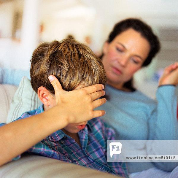 Frau und Kind mit Hand auf dem Kopf