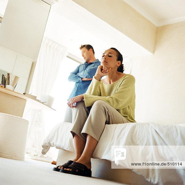 Mann stehend mit gekreuzten Armen  hinter Frau auf Bettkante sitzend  Blickwinkel niedrig